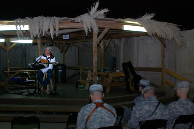 """Salado, Texas native, Freddie Fuller sings for Soldiers at the Pegasus Dining Facility at Camp Liberty in western Baghdad, Nov. 12. Fuller, who calls himself the """"Singing Cowboy,"""" performed the last of his seven-concert tour outside the 1st Cavalry Division's dining facility."""""""