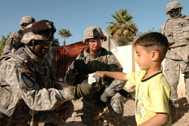 Command Sgts. Maj. James Daniels (left), the senior noncommissioned officer with the 4th Squadron, 9th Cavalry Regiment, 2nd Brigade Combat Team, 1st Cavalry Division and Neil Ciotola, the Multi-National Corps - Iraq command sergeant major, hand out toys to children in a western Baghdad neighborhood Nov. 13.