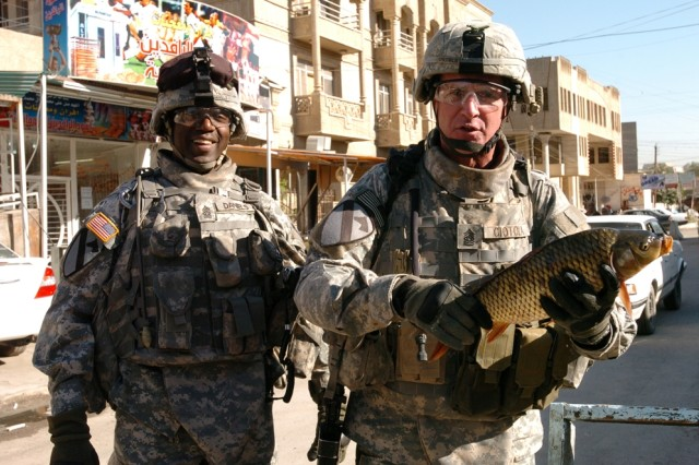Command Sgt. Maj. Neil Ciotola (right), the senior noncommissioned officer for the Multi-National Corps - Iraq, holds up a fish during a walk-through of a market in western Baghdad along with Command Sgt. Maj. James Daniels, the top NCO with 4th Squadron, 9th Cavalry Regiment, 2nd Brigade Combat Team, 1st Cavalry Division, Nov. 13.