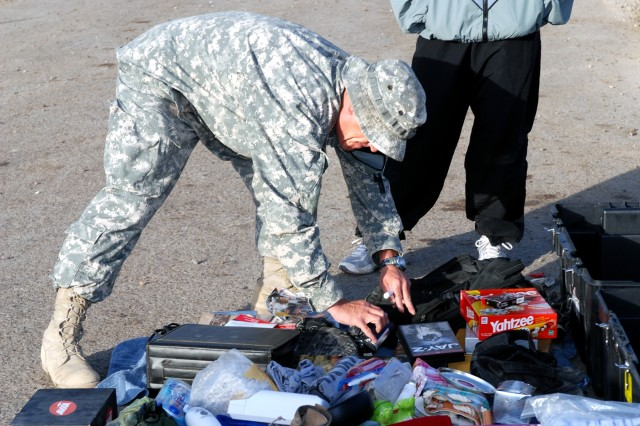 Indianapolis native Staff Sgt. Veral Sullivan, a training noncommissioned officer with Headquarters and Headquarters Company, Special Troops Battalion, 1st Cavalry Division, checks a Soldier's belongings to make sure the items will clear a customs inspection at their battalion's motor pool on Camp Liberty in western Baghdad, Nov. 15.