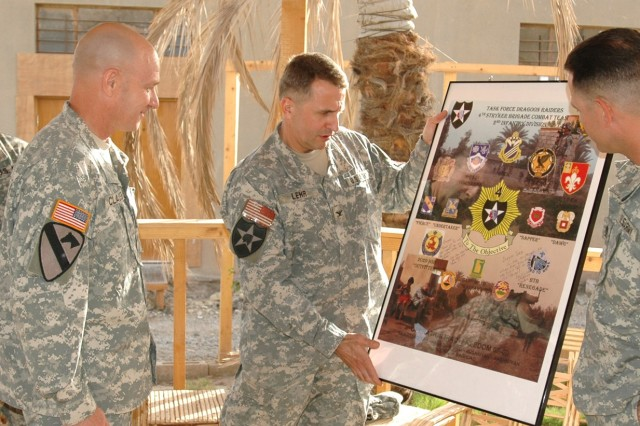 Dover, Pa., native Col. Jon Lehr (center), commander, 4th Stryker Brigade Combat Team, 2nd Infantry Division presents a 4th SBCT poster to 1st Battalion, 82nd Field Artillery senior leaders, San Diego native Lt. Col. Martin Clausen (left), 1-82 commander, and Command Sgt. Maj. Mike Giles, the unit's senior noncommissioned officer, who hails from Omaha, Neb., during a ceremony on Camp Taji, Iraq Nov. 13. Lehr presented the poster in appreciation for the fire support the field artillery battalion has given to Lehr's brigade.