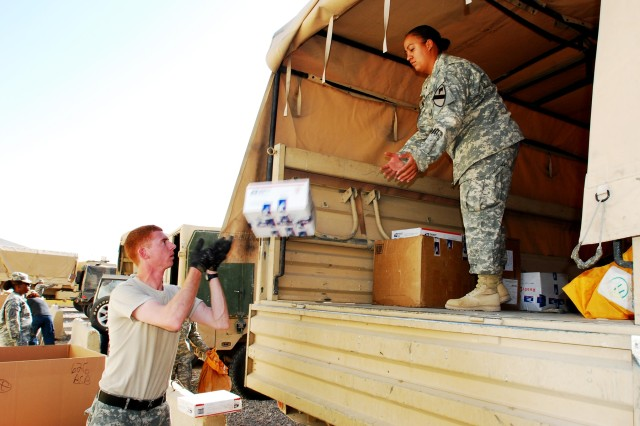 Grover Beach, Calif., native, Spc. Vincent Daly, mail clerk for Headquarters and Headquarters Company, 1st Cavalry Division, tosses a parcel to Brooklyn, N.Y., native, Spc. Osiris Roman, member of the supply section for the same unit, at the Joint Military Mail Terminal at the Baghdad International Airport, Nov. 14. Members of the supply section take turns to help Daly with his mail room responsibilities.