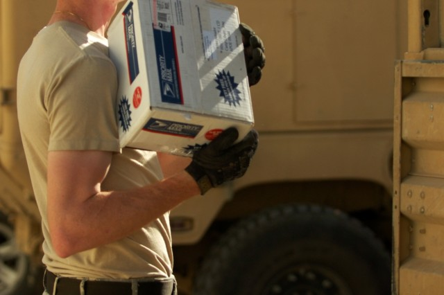 Grover Beach, Calif., native Spc. Vincent Daly, a mail clerk with Headquarters and Headquarters Company, 1st Cavalry Division waits for his partner to finish setting one of the parcels in the truck at the Joint Military Mail Terminal at Baghdad International Airport, Nov. 14.