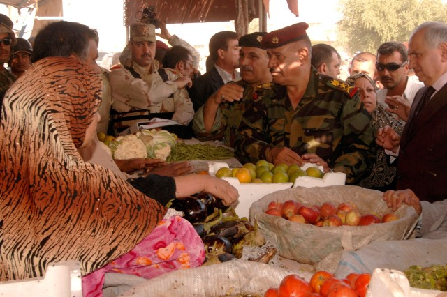 Iraqi Army Lt. Gen. Abud Qanbar, commander, Baghdad Operations Command, and Dr. Ahmed Challabi, Operation Fahrd Al Qanoon services committee chairman, chat with local residents at a market in Sab Al Bor, Iraq Nov. 17 about improved security in the area.