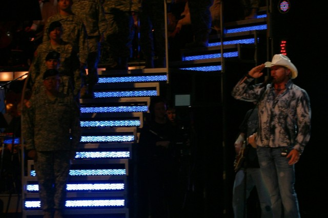 """Country music star Toby Keith salutes Fort Sill Soldiers who were onstage to accompany Keith while he sang """"American Soldier"""" at the Oklahoma Centennial Spectacular Nov. 16 in Oklahoma City."""