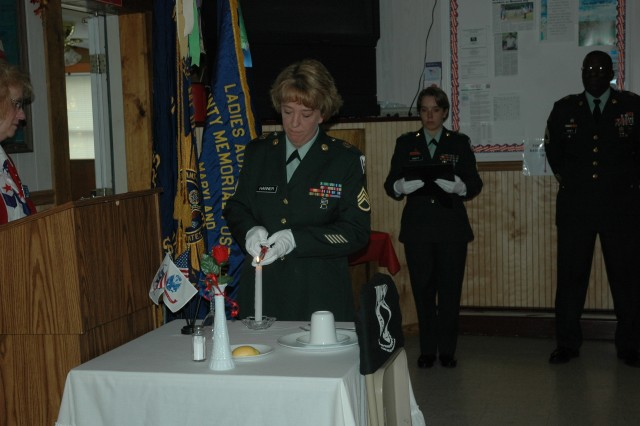 Staff Sgt. Rebecca Hanner, RDECOM operations noncommissioned officer for the command sergeant major, lights a candle on the POW/MIA table in remembrance of prisoners of war and Soldiers missing in action Nov.12, at a ceremony at VFW 5337 in Abingdon, Md.