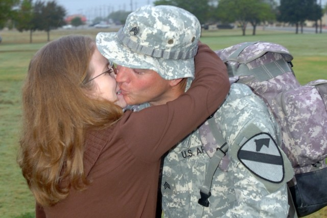 Gadsden, Tenn., native Lori Hall welcomes home her husband, Tampa, Fla., native Sgt. Eric Hall, with Company F, 2nd Battalion, 227th Aviation Regiment, 1st Air Cavalry Brigade, 1st Cavalry Division, with a big hug and kiss during a welcome home ceremony Nov. 19 on Cooper Field at Fort Hood, Texas. About 10 troopers from the brigade returned to Fort Hood after serving more than a year in Iraq.