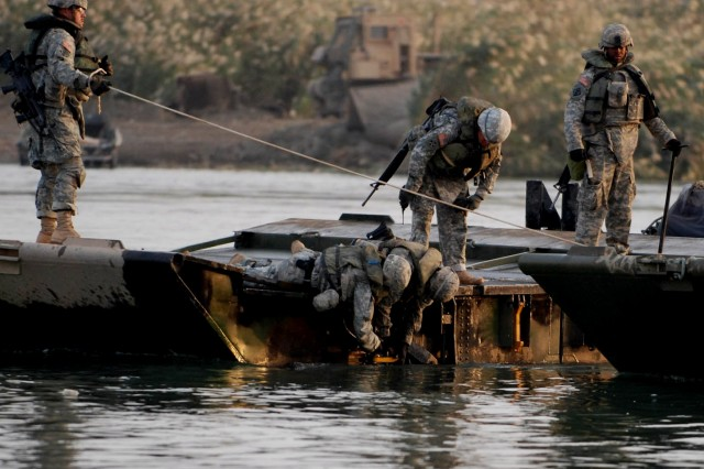 Soldiers from U.S. Army Europe's 502nd Engineer Company lock assault float bridge bay sections together to ferry vehicles and heavy equipment across the Euphrates River in support of Operation Marne Courageous Nov. 16.