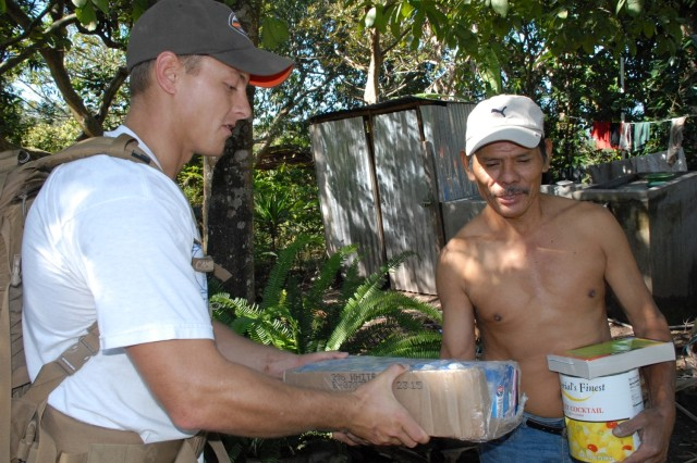 Air Force 1st Lt. Timothy Brodman delivers food to a local Honduran at La Sampedrana, during a mountain hike.