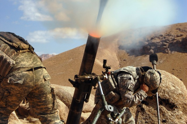 Pfc. Jerry Cleveland (left) and Spc. Brett Mitchell, with the International Security Assistance Force, fire a 120 mm mortar during a combat operation in the Da'udzay Valley in Zabol Province, Afghanistan.