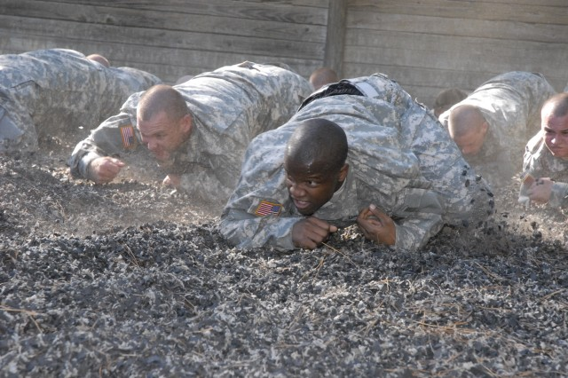 Pvt. Christopher Vann, a Basic Combat Training Soldier assigned to Company C, 2nd Battalion, 13th Infantry Regiment, executes a low crawl Thursday at the Fit to Win Course I on his first day of training. The company was brought to the course immediately after being picked up from the 120th Adjutant General Battalion (Reception).