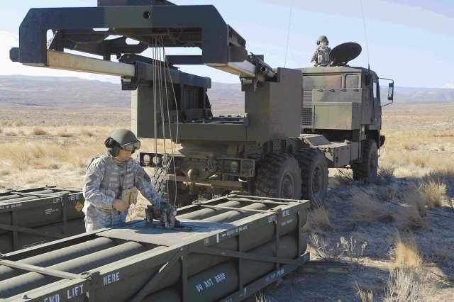 """Staff Sgt. Chris Starnes unloads a training rocket pod and prepares to load a live pod while driver Spc. Brady Smith watches from the hatch of the vehicle during a HIMARS live fire at Yakima Training Center."""""""