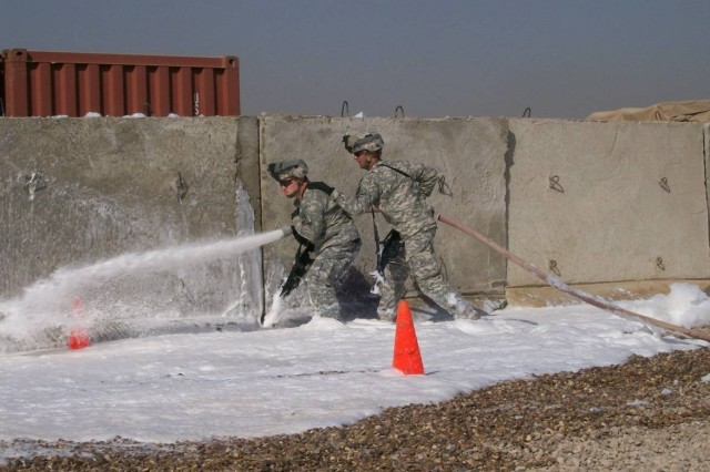 Pfc. Eric Beavers and Sgt. Steven Thompson, both with Bravo Company, 526th Brigade Support Battalion, practice maneuvering with a fire hose and foam-liquid fire-extinguisher solution during their Firefighting Certification Course.