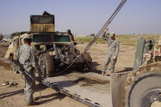After the flames are extinguished, Sgt. Carlos Rodriguez and Pfc. Derrick Horton, both from Bravo Company, 526th Brigade Support Battalion, load a damaged vehicle onto a flat rack using the palletized loading system hook.
