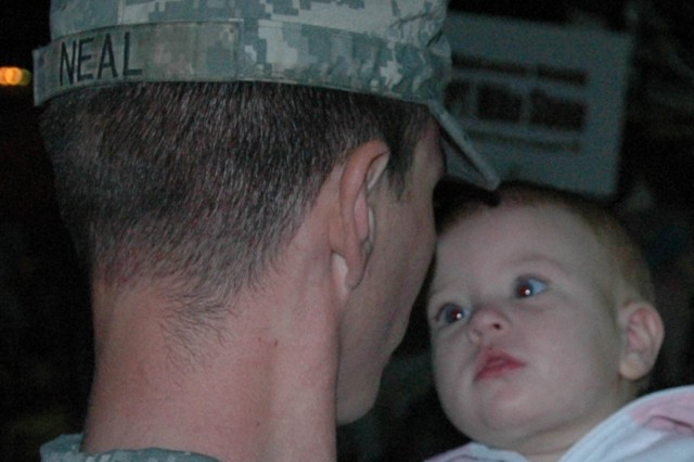 Ten-month-old Grace Neal looks into her father's eyes, Sgt. Russell Neal, an apache mechanic with 4th Battalion, 227th Aviation Regiment, 1st Air Cavalry Brigade, 1st Cavalry Division, for the first time since she was 8-weeks old at a homecoming ceremony held on Fort Hood's Cooper Field Nov. 21. Her mother, Jamie Neal, said she was very anxious to see how Grace would take seeing her father after only hearing his voice over the phone for the past eight months.