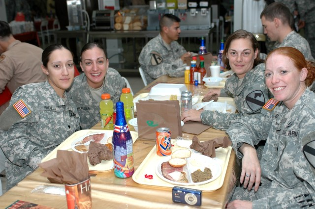 "(Left to right) Spcs. Christina Padilla, from Los Angeles; Dawn Murgia, of Waldorf, Md.; Lynn Hansford, from Oldtown, Md.; and Mindy Saindon, of Derby, Kan., ham it up at the Thanksgiving meal at the Command Sgt. Maj. Cooke Dining Facility Nov. 22 at Camp Taji, Iraq. The Soldiers, from the 3rd ""Spearhead"" Battalion, 227th Aviation Regiment, 1st Air Cavalry Brigade, 1st Cavalry Division, had mixed feelings about serving in Iraq for a second consecutive Thanksgiving."