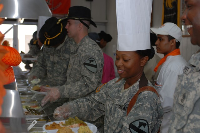"Canton, Miss., native Capt. Katina Sutton, commander of the Command Post Detachment, Division Special Troops Battalion, 1st Cavalry Division, serves Thanksgiving dinner to Soldiers in the Pegasus Dining Facility at Camp Liberty in western Baghdad, Nov. 22. Several ""First Team"" officers and senior noncommissioned officers took part in serving the meal to Soldiers in the DFAC."