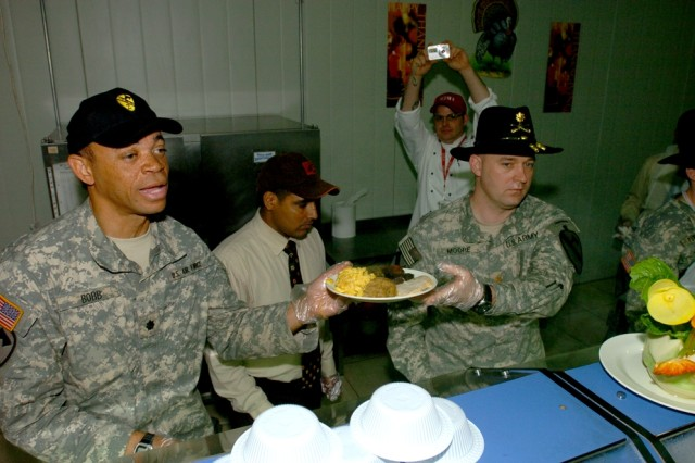 Air Force Lt. Col. Justin Bobb (left), 2nd Brigade Combat Team's electronic warfare officer, and Maj. Lance Moore, the Black Jack Brigade's operations officer, serve the troops at the Black Jack Bistro Dining Facility on Forward Operating Base Prosperity in central Baghdad, Nov. 22.