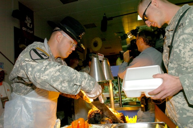 "Capt. Lexie R. Gibbs III, commander of Headquarters and Headquarters Company, 2nd ""Black Jack"" Brigade Combat Team, 1st Cavalry Division, carves a piece of pot roast for a Soldier during the Thanksgiving Day meal at the Black Jack Bistro Dining Facility on Forward Operating Base Prosperity in central Baghdad, Nov. 22."
