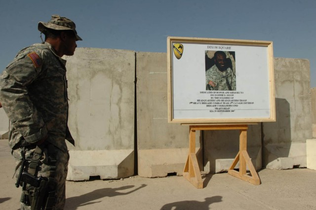 Staff Sgt. Mario Whitaker, non-commissioned officer in charge of the brigade commander's Personal Security Detachment, 3rd Brigade Combat Team, 1st Cavalry Division, looks at the memorial picture of Staff Sgt. Donnie Dixon, a good friend and fellow Soldier of Whitiker's, during the dedication of Dixon Square ceremony.  The Dixon Square is an area for Soldiers to relax and have fun while serving in Diyala province, Iraq, and is a reminder of Dixon's service during Operation Iraqi Freedom 06-08.