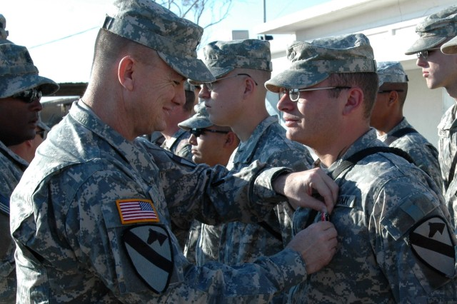 "Col. Paul E. Funk II, commander, 1st ""Ironhorse"" Brigade Combat Team, 1st Cavalry Division, presents the Bronze Star Medal with ""V"" device for valor to Raymond, N.H., native Spc. Nathaniel Patterson of Company D, 2nd ""Stallion"" Battalion, 8th Cavalry Regiment during an award ceremony at Camp Taji, Iraq Nov. 23. Patterson received the medal for actions taken while under enemy fire in Tarmiyah, Iraq Feb. 19 during an engagement with insurgents in which he administered medical aid to his fellow Soldiers."