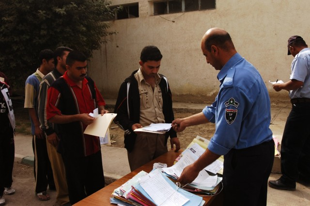 An Iraqi police officer checks in applicants at a police recruitment drive, which was held in Karkh Nov. 16.