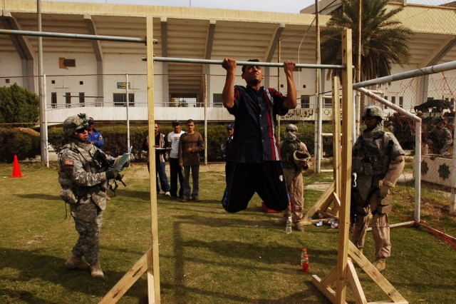 Sgt. Brian McCain, Headquarters and Headquarters Troop, 4th Squadron, 2nd Stryker Cavalry Regiment, attached to the 2nd Brigade Combat Team, 1st Cavalry Division, watches as a Karkh resident who hopes to join the Iraqi police force, performs pull-ups during a physical fitness test as part of a police recruitment drive that was held in the area Nov. 16.