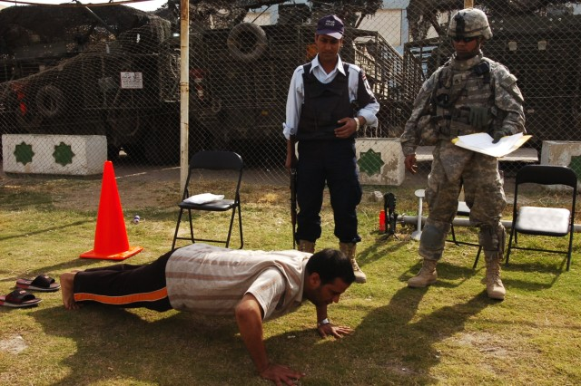 An applicant performs push-ups as part of the physical fitness test given to potential Iraqi police recruits, while a police officer and Staff Sgt. Edmund Savedra, with Headquarters and Headquarters Troop, 4th Squadron, 2nd Stryker Cavalry Regiment, attached to the 2nd Brigade Combat Team, 1st Cavalry Division look on, during a police recruitment drive, which was held in Karkh Nov. 16.