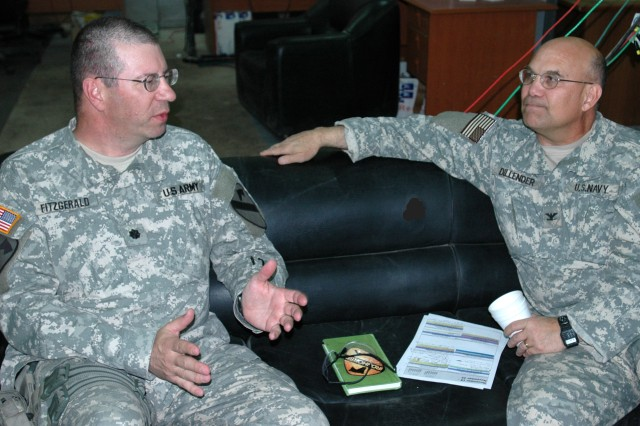 "Lt. Col. Harvey Fitzgerald (left), senior agri-business advisor for the 1st ""Ironhorse"" Brigade Combat Team, 1st Cavalry Division's Embedded Provincial Reconstruction Team (EPRT Baghdad 5) and Navy Capt. John Dillender, economics and industrial advisor also with EPRT Baghdad 5, share in a discussion, about the assassination of President John F. Kennedy, at Camp Taji, Iraq Nov. 22. This year marked the 44th anniversary of the assassination and both Fitzgerald, a Hermosa, S.D. native, and Dillender, who calls Henning, Tenn. home, can clearly remember where they were and what they were doing November 22, 1963 when the president was shot in Dallas."