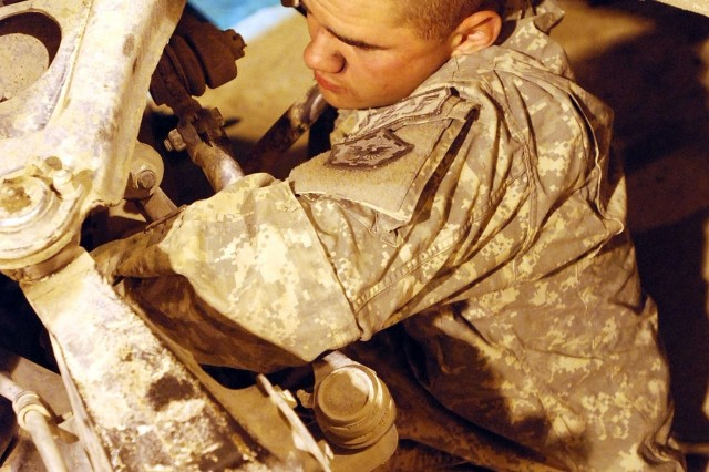 Army Pfc. Carson Beaver, a mechanic from Headquarters Support Company, 864th Engineer Battalion strains to reach into the engine of a Humvee that needs repair at Forward Operating Base Sharana, Afghanistan, Nov. 7.