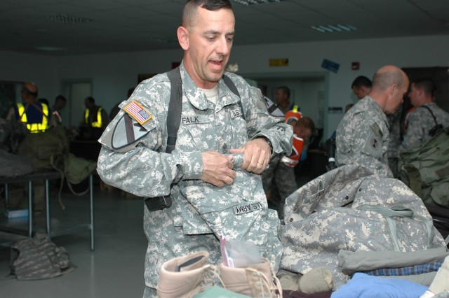 """Boulder, Colo., native 1st Sgt. David Falk, the senior enlisted Soldier for Company C """"Witch Doctors,"""" 2nd Battalion, 227th Aviation Regiment, 1st Air Cavalry Brigade, 1st Cavalry Division, rolls up his clothes as he puts them back in his bag after a customs inspection in Balad, Iraq, Nov. 18. After a nearly 15-month deployment, the Witch Doctors, 1st Cav. Div.'s medical evacuation unit, are headed home to Fort Carson, Colo. Falk is looking forward to seeing his family and eating anything that isn't mass produced and consumed with a plastic utensil, he said."""