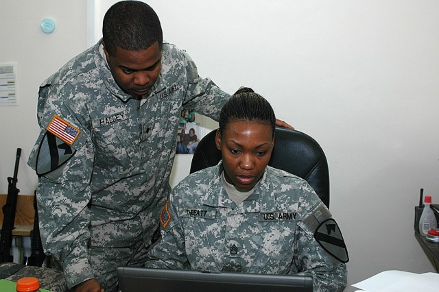 Staff Sgt. Rosie Threatt, senior Human Resources noncommissioned officer for the 1st Air Cavalry Brigade, 1st Cavalry Division, (right), discusses personnel actions with New Orleans native Spc. Troy Halley, Human Resources information specialist, (left), Nov. 19 at Camp Taji, Iraq. Threatt, a Port Gibson, Miss., native, joined the Army in 1999 to get a college education and make a better life for her family.