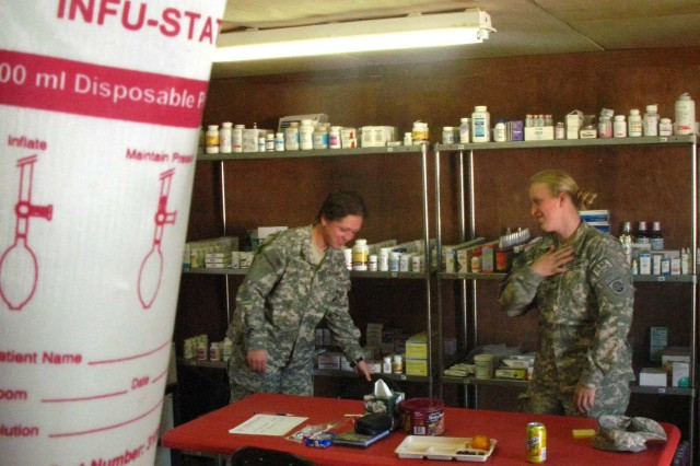 Army medic Pfc. Megan Anstiss (left) helps cover the duties in the aid station with another Soldier at Forward Operating Base Shank during Army Spc. Cassandra Miles absence.