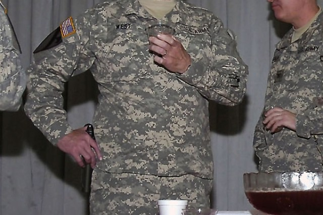 """Richmond, Ky., native and co-host of the St. Barbara induction ceremony, Col. Billy Jack West, commander, 138th Field Artillery Brigade, Kentucky Army National Guard, tries the """"artillery punch"""" to make sure it's fit for consumption for the inductees. Twenty-one new members were inducted into the Order of St. Barbara during the event, held at the Al-Faw Palace at Camp Victory in western Baghdad, Nov. 23."""