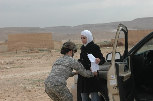 A female Soldier practices searching an Arabic woman at a checkpoint during a cultural-awareness situational-training exercise.