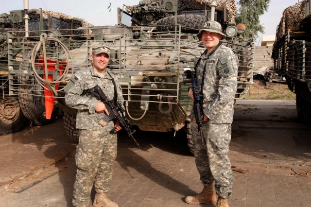 Spc. Alex Lamont Garner of U.S. Army Europe's 1st Squadron, 2nd Stryker Cavalry Regiment (left) poses for a photo with his brother, Capt. Phillip Garner of the 2nd Battalion, 319th Airborne Field Artillery, at Coalition Outpost War Eagle, Iraq.  Phillip was already deployed when Alex found out he was headed for Iraq.
