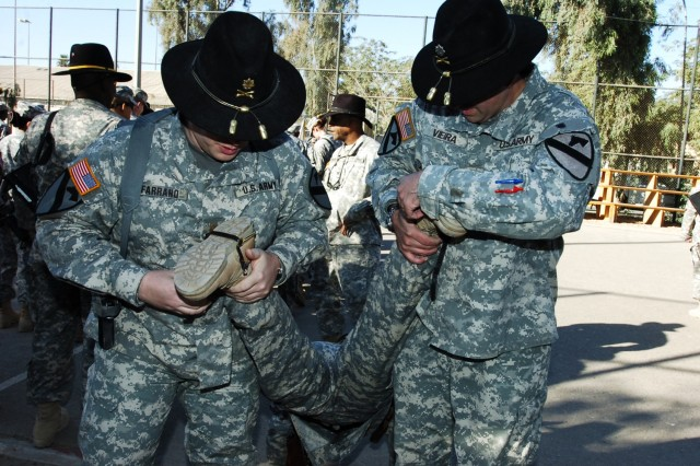 Maj. Dale Farrand (left), the executive officer for the 15th Brigade Support Battalion, 2nd Brigade Combat Team, 1st Cavalry Division, and the 15th BSB commander, Lt. Col. Jeffrey Vieira, strap on a pair of gold combat spurs to the boots of one of their Soldiers during an awards ceremony at Forward Operating Base Prosperity in central Baghdad, Nov. 27.