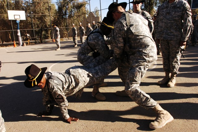1st Sgt. Tonia Littlejohn, the top noncommissioned officer for Headquarters and Headquarters Company, 15th Brigade Support Battalion, 2nd Brigade Comb at Team, 1st Cavalry Division, assumes the front-leaning rest position as Command Sgts. Maj. Nathaniel Richardson (left) and James Lee strap on her gold combat spurs during an awards ceremony at Forward Operating Base Prosperity in central Baghdad, Nov. 27.