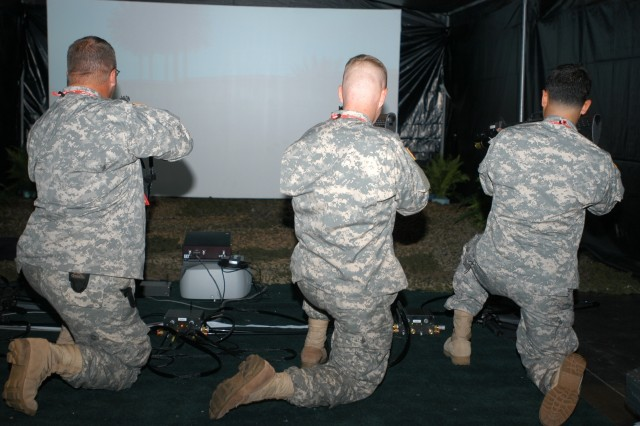 Soldiers from the 143rd Sustainment Command (Expeditionary) respond as sniper fire erupts from a rooftop in a weapons-training simulator.