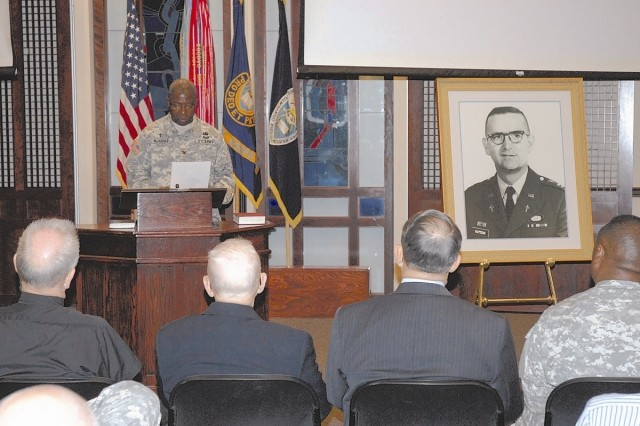 Chaplain (Col.) Clarke McGriff, commandant of the Army Chaplain Center and School, reads remarks from Chaplain (Maj. Gen.) Douglas Carver, Army chief of chaplains, Nov. 20, regarding the heroic efforts of Chaplain (Maj.) Charles Watters during the Vietnam War. The school has been dedicated in Chaplain Watters' memory as Watters Hall.  ""