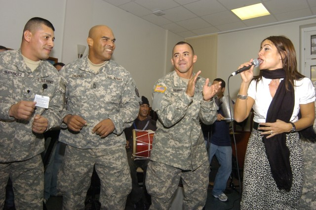 Entertainer Melina Leon recruits three Soldiers into backup duty during her Nov. 29 performance at Landstuhl Regional Medical Center. Leon joined fellow singer Jamie O'Neal and the New England Patriots cheerleaders to visit servicemembers downrange and in Europe as part of Operation Season's Greetings.