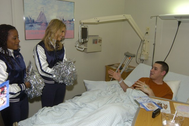 Stacey McIntyre (left) and Megan White spend time with Specialist Robert Hammond during his stay at Landstuhl Regional Medical Center. The New England Patriots cheerleaders joined with singers Melina Leon and Jamie O'Neal to visit servicemembers downrange and in Europe as part of Operation Season's Greetings.