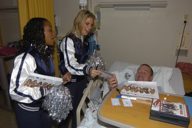 Stacey McIntyre (left) and Megan White pay a surprise visit to Private Jacob Morton during his stay at Landstuhl Regional Medical Center. The New England Patriots cheerleaders joined with singers Melina Leon and Jamie O'Neal to visit servicemembers downrange and in Europe as part of Operation Season's Greetings.