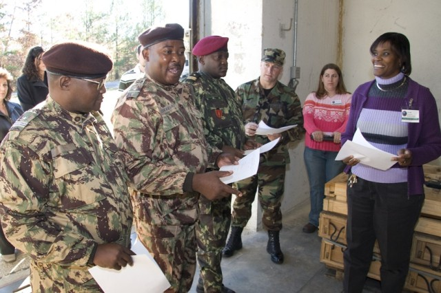 Mozambique military officers tour the storage and inventory operations of the Anniston Defense Munitions Center Wednesday. Here, (l-r) Col. Daniel Melaco Anastacio, chief of operations for the Mozambique army; Maj. Jose Correia Junior, who works in the Mozambique Army field artillery branch and serves as interpreter; and Lt. Col. Eugenio Roque, commanding officer of the Mozambique Army Special Forces Training Center; and U.S. Air Force Master Sgt. Richard Phillips, U.S. Embassy in Mozambique, receive information about ADMC's storage procedures from Flouzetta Hill (far right), storage operations supervisor at one of the igloos. Also pictured is Amie Lackey who provided the visitors with munitions inventory procedures.
