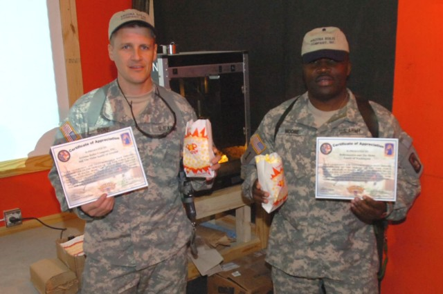 Task Force Ready Commander Lt. Col. Jack Bone and Command Sgt. Maj. John Moore enjoy some freshly popped corn Nov. 22 while dedicating the 5th Bn., 158th Aviation Regt., Mission Ready Theater.  To help fix up the space, friends and family members of the unit donated more than $4,000 worth of equipment, including a theater-style popcorn machine.