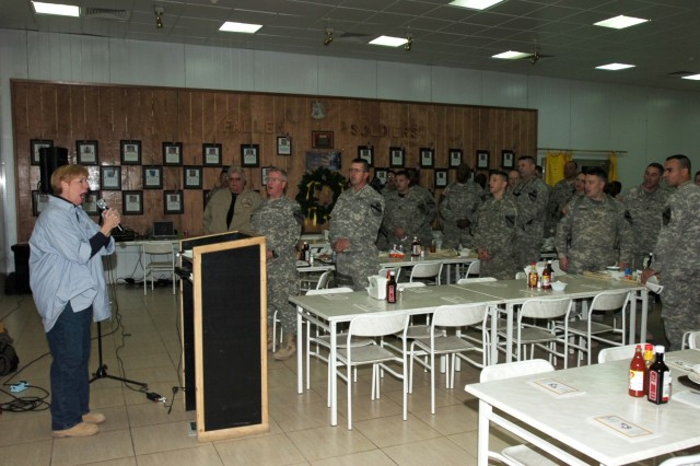 "Soldiers from the 2nd Brigade Combat Team, 1st Cavalry Division join Betsy Brown, the founder of Heartsong Ministries, a non-profit organization in Texas, for a rendition of ""God Bless America"" during a prayer luncheon at Forward Operating Base Prosperity's Black Jack Bistro in central Baghdad Nov. 27."""