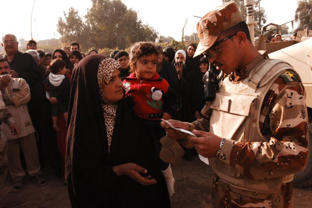 """An Iraqi army soldier looks over the identification of a Quds Camp resident during a kerosene heater and blanket distribution to residents in the central Baghdad Janeen neighborhood, Nov. 29."""""""
