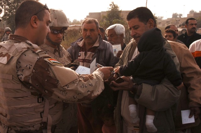 """An Iraqi Army soldier checks the identification of a man before he enters the distribution site at the Quds Camp in central Baghdad's Janeen neighborhood during a kerosene heater and blanket distribution conducted by Soldiers from 3rd Battalion, 82nd Field Artillery Regiment, 2nd Brigade Combat Team, 1st Cavalry Division, Iraqi Army troops and members of the local neighborhood advisory council, Nov. 29."""""""