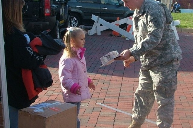 Lyssa Kagel, 5, of Baltimore chose Sgt. Rieman's action figure for her prize after successfully completing the football toss.