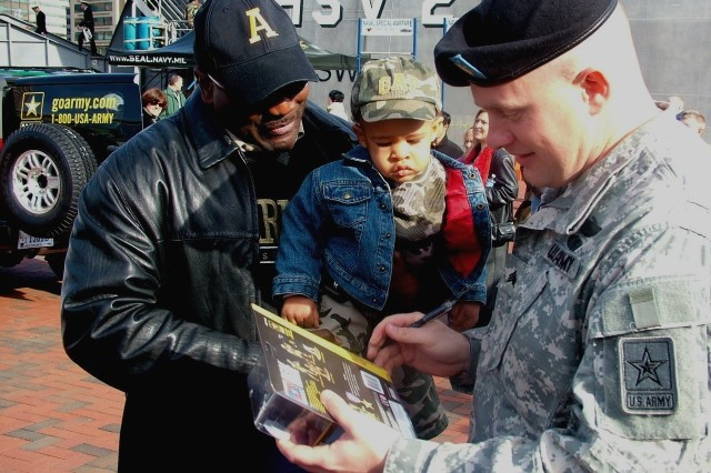 Sgt. Tommy Rieman signs his action figure as Patrick Johnson and 18-month-old eagerly await a new toy.  Sgt. Rieman was handing out action figures in the Baltimore Inner Harbor the Friday and Saturday of the Army-Navy game.""